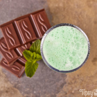 top view of a grasshopper shot with chocolate pieces and mnit leaves on a natural tile background