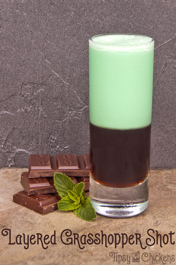 dshooter glass filled with dark creme de cacao with green creme de menthe and cream shaken together and layered over top with chocolate and fresh mint garnish