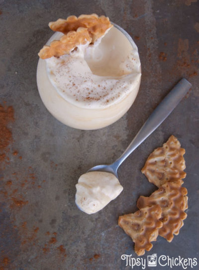 top view of glass of rumchata mousse with a spoonful scooped out on a spoon sitting on a mottled tile with sprinkles cinnamon and broken up pieces of vanilla pizzelle