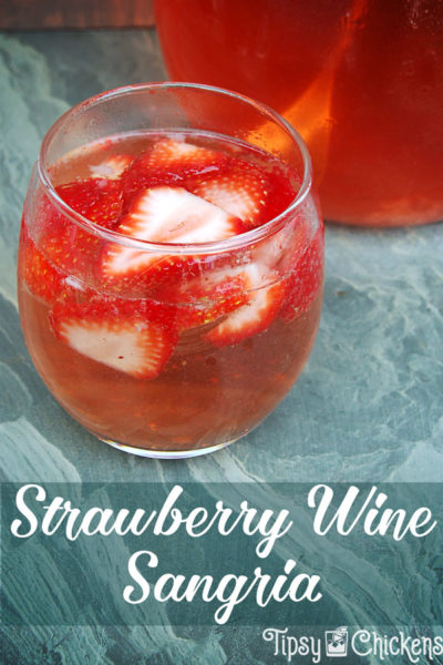 strawberry wine sangria in a clear rounded glass with sliced of fresh strawberries on a green marbled tile