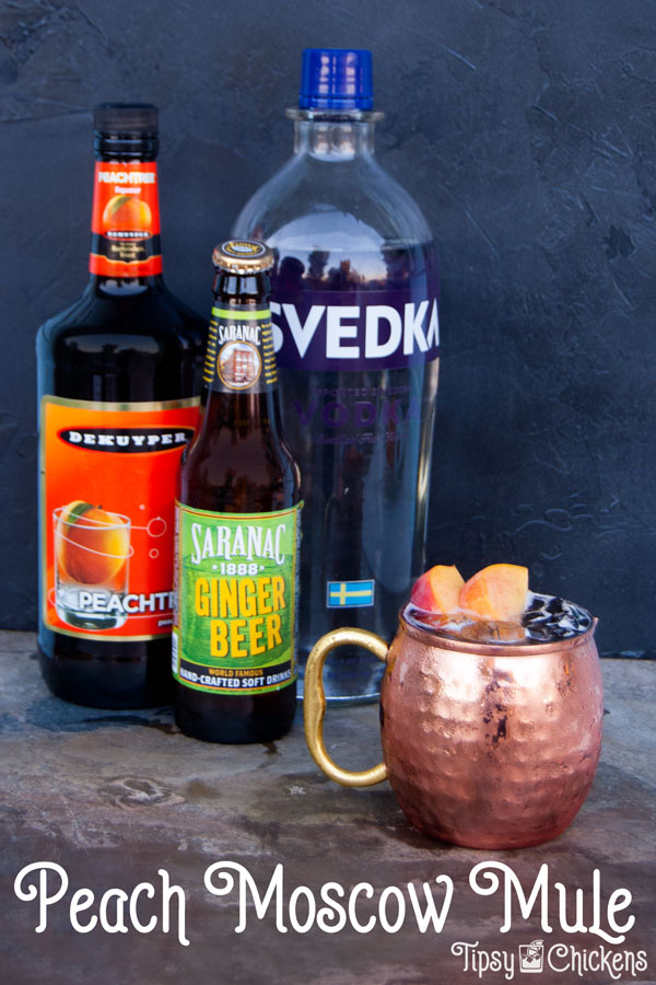 each mocow mule in hammered copper cup with bottle of peach schnapps, vodka and saranac ginger beer in the background