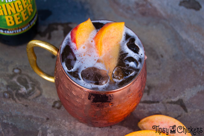 each Moscow mule in hammered copper cup with peach slice garnish and saranac ginger beer in the background