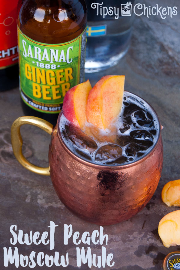 each mocow mule in hammered copper cup with peach slice garnish and saranac ginger beer in the background
