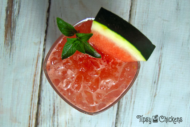watermelon gin smash in a square rocks glass with a slice or watermelon and a sprig of mint