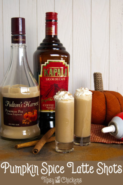 two tall shot glasses filled with pumpkin spice latte shots topped with whipped cream and a sprinkle of cinnamon on a mottled tile back ground with cinnamon sticks, a fabric pumpkin, Fulton's harvest pumpkin liqueur, kapali coffee liqueur and whipped cream in the background