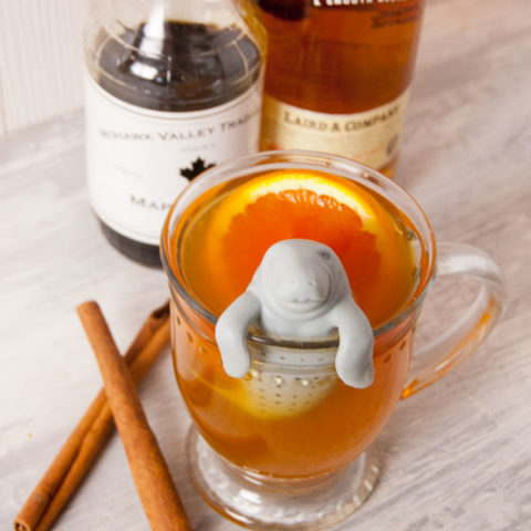 clear glass mug filled with Applejack and Ornage Hot toddy with Manatea tea strainer and bottles of maple syrup and applejack in the background on an aged white wooden surface wit h two crossed cinnamon sticks