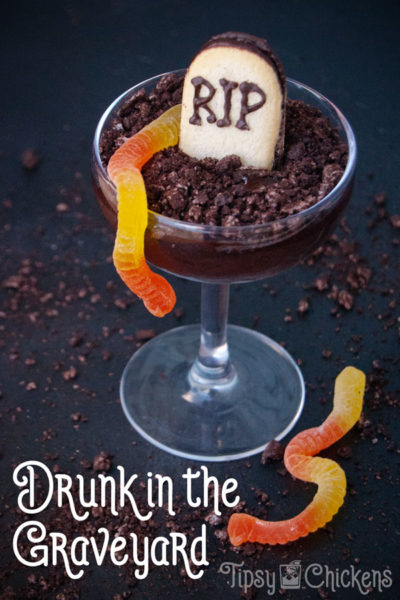 coupe glass filled with dark chocolate pudding made with alcohol with a tombstone cookie, crushed oreos and gummy worms