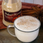 milk and pumpkin pie cream liqueur in a large clear coffee mug on a natural tile with a bottle of Fulton's Harvest Pumpkin Pie Cream Liqueur,