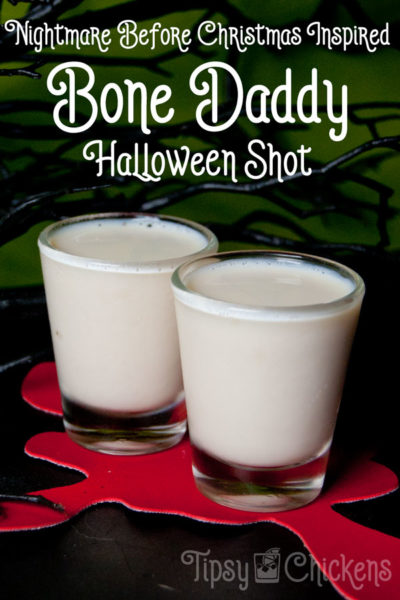 two shot glasses filled with white Bone Daddy Shots made from rumchata and black rum sitting on a red blood splatter coaster with a bright green bachground with spooky black branches and text overlay Nightmare Before Christmas Inspired Bone Daddy Halloween Shot