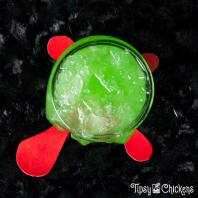 top view of clear skull glass filled with crushed ice, rum, pineapple juice, Midori, blue Curacao with two red maraschino cherries for eyes on a black surface over a red blood splatter coaster