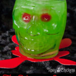 clear skull glass filled with crushed ice, rum, pineapple juice, Midori, blue Curacao with two red maraschino cherries for eyes on a black surface over a red blood splatter coaster