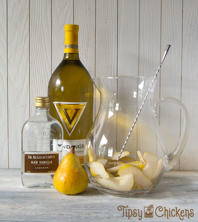 glass pitcher with a bottle of chardonnay, a pear and a bottle of vanilla schnapps