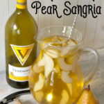 glass pitcher filled with sliced pears and white wine pear sangria with a bottle of chardonnay, a pear and a wine bottle opener