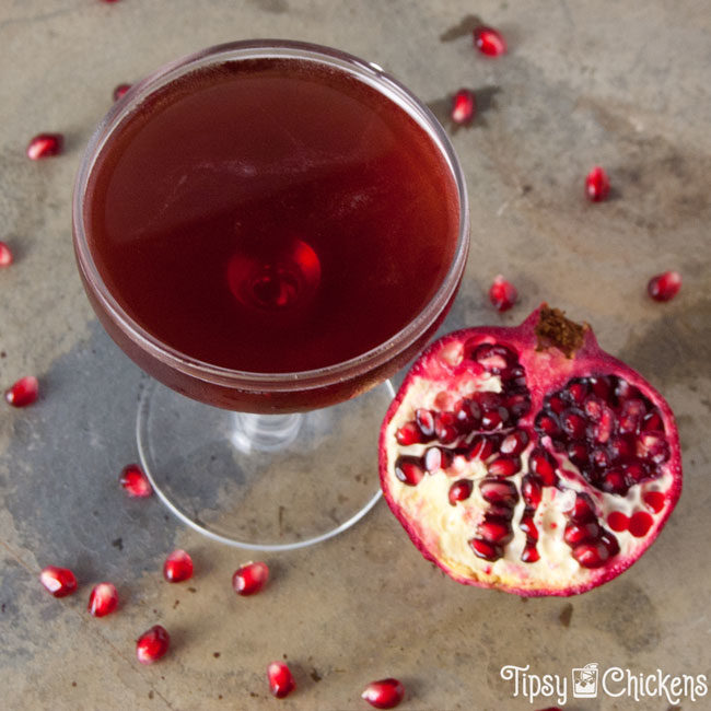 top view of a winter rose cocktail, a jack rose variation with pomegranate juice, shown with half a pomegranate and scattered pomegranate arils