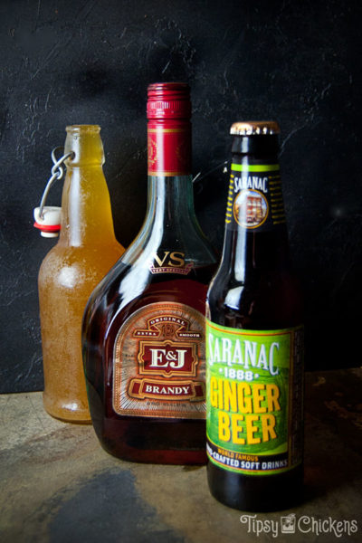 bottle of Saranac root beer, bottle of E&J brandy and flip top bottle apple cider