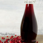 homemade grenadine in a curvy glass bottle on a green stone tile with pomegranate seeds and a white background