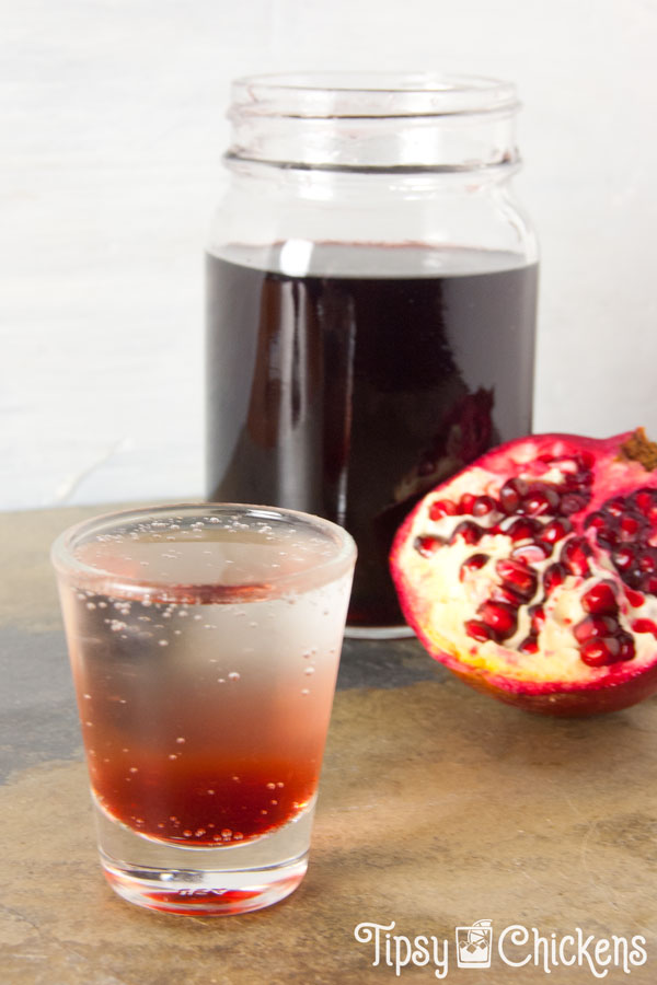 shot glass filled with clear soda with grenadine at the bottom with a mason jar full of grenadine in the background with half a pomegranate leaning on it