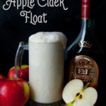 tall glass filled with vanilla ice cream, brandy, apple cider and ginger beer with a bottle of brandy and apples in the background and a single cut in half apple in front against a black background