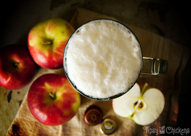 top view of spiked apple cider float made with brandy, apple cider and ginger beer with apples in the background