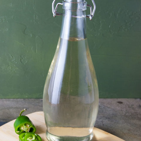 clear bottle filled with clear but slightly greenish tequila infised with jalapeno peppers sitting on a cutting board with a slided jalapno pepper to the left