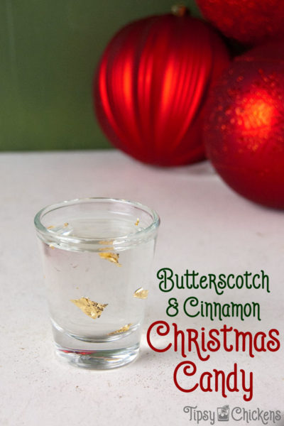 single shot glass filled with Goldschläger, Buttershots and edible gold leaf on a white tile surface with a green background and red Christmas balls