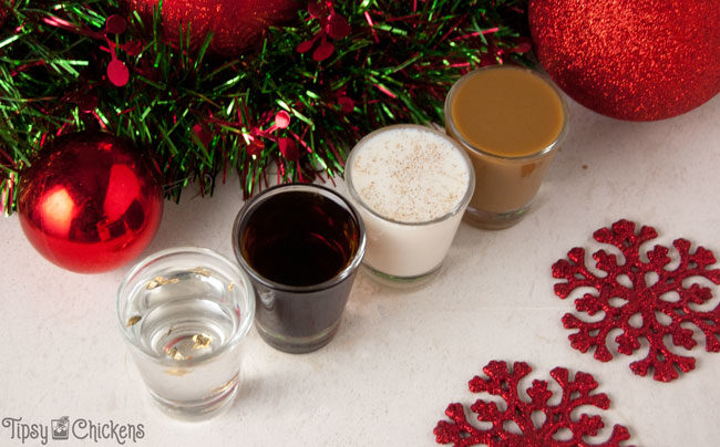 four shot glasses lined up on a white tile filled with different Christmas shots with red glitter snowflakes, red Christmas ornaments and a metallic red and green Christmas garland in the background