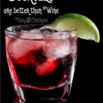 Cranberry and lime cocktail on the rocks in a rocks glass against a black background