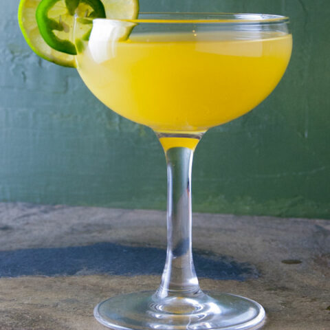 cocktail made with jalapeno tequila, pineapple juice and lime juice with a line wheel and jalapeno garnish against a green background