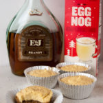 bottle of brandy, carton of eggnog and four mini no bake eggnog cheesecakes spiked with brandy and sprinkled with nutmeg