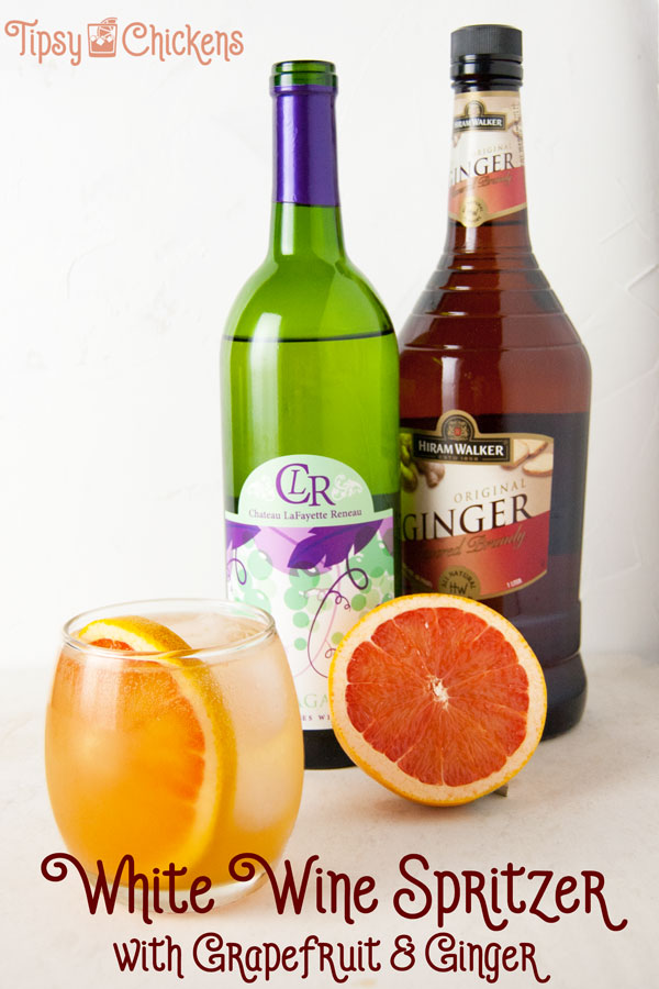 white wine spritzer with grapefruit juice, ginger brandy and club soda in a glass with a grapefruit slice and ice cubes infront of half a pink grapfruit, a bottle of Niagra white wine and a bottle of ginger brandy