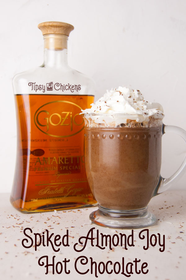 hot chocolate in a glass mug made with coconut milk, bakers chocolate, amaretto and coconut syrup topped with whipped cream and chocolate shavings with amaretto bottle in the background