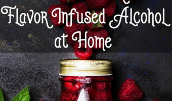 class jar filled with raspberries and vodka against a dark splattered background with raspberries and raspberry leaves in the background