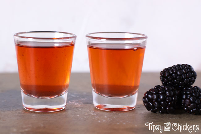 strained american honey blackberry whiskey in two shot glasses