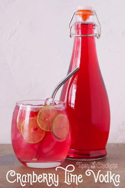 bottle of cranberry and lime infused vodka in a glass bottle with a clear glass cup filled with  ice, lime slices and cranberry lime vodka soda with a metal straw