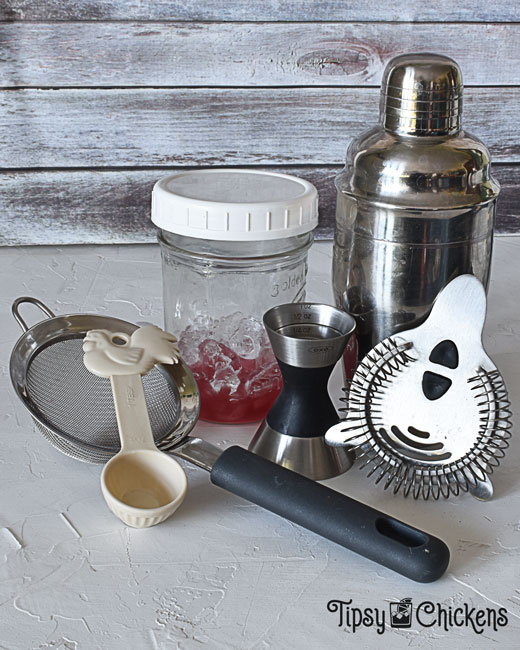 cocktail shaker, mason jar with screw on lid, jigger, hawthorn strainer, tablespoon and strainer set up to show how to make a home bar out of things you already have