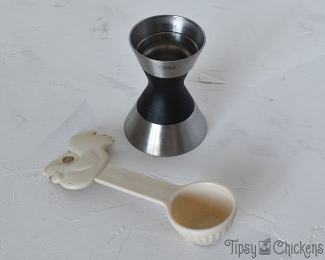 OXO jigger and an off white tablespoon with a chicken on the top