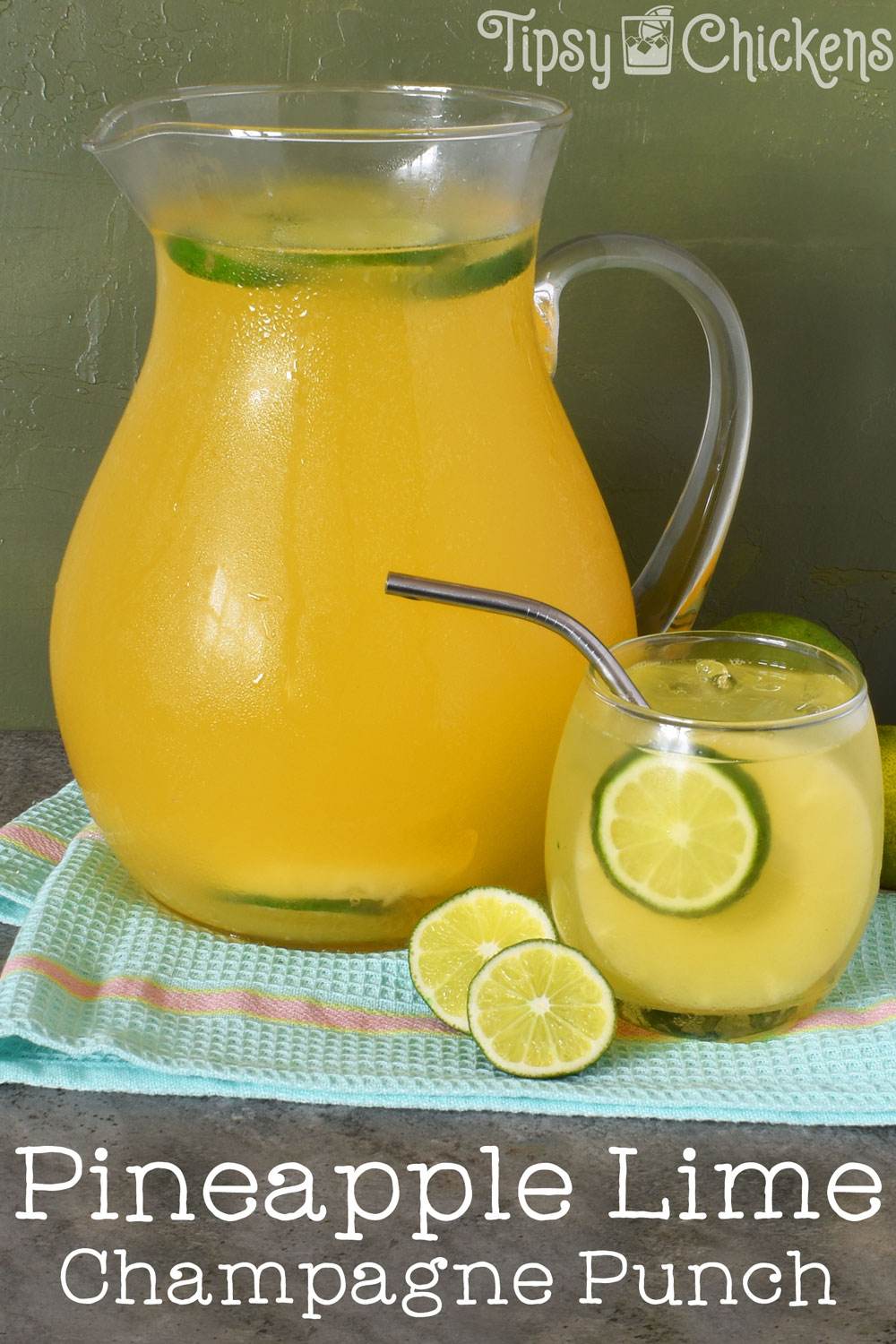 glass pitcher filled with pineapple juice, lime juice, ginger brandy, champagne and seltzer to make pineapple champagne punch on a blue towel over a grey tile with a rounded glass filled with champagne punch, a pineapple slice and a lime slice with a metal straw