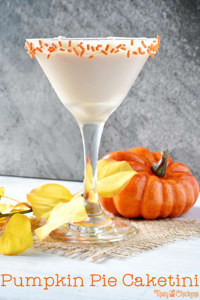 pumpkin pie cocktail in a martini glass with a frosting & sprinkle decorated rim
