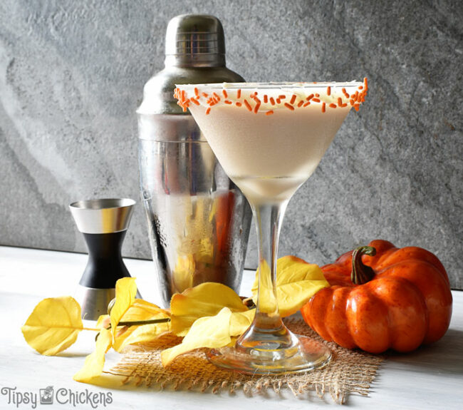 autumn pumpkin pie cocktail in a martini glass with a frosting and orange sprinkle rim with a cocktail shaker, jigger and fake pumpkin