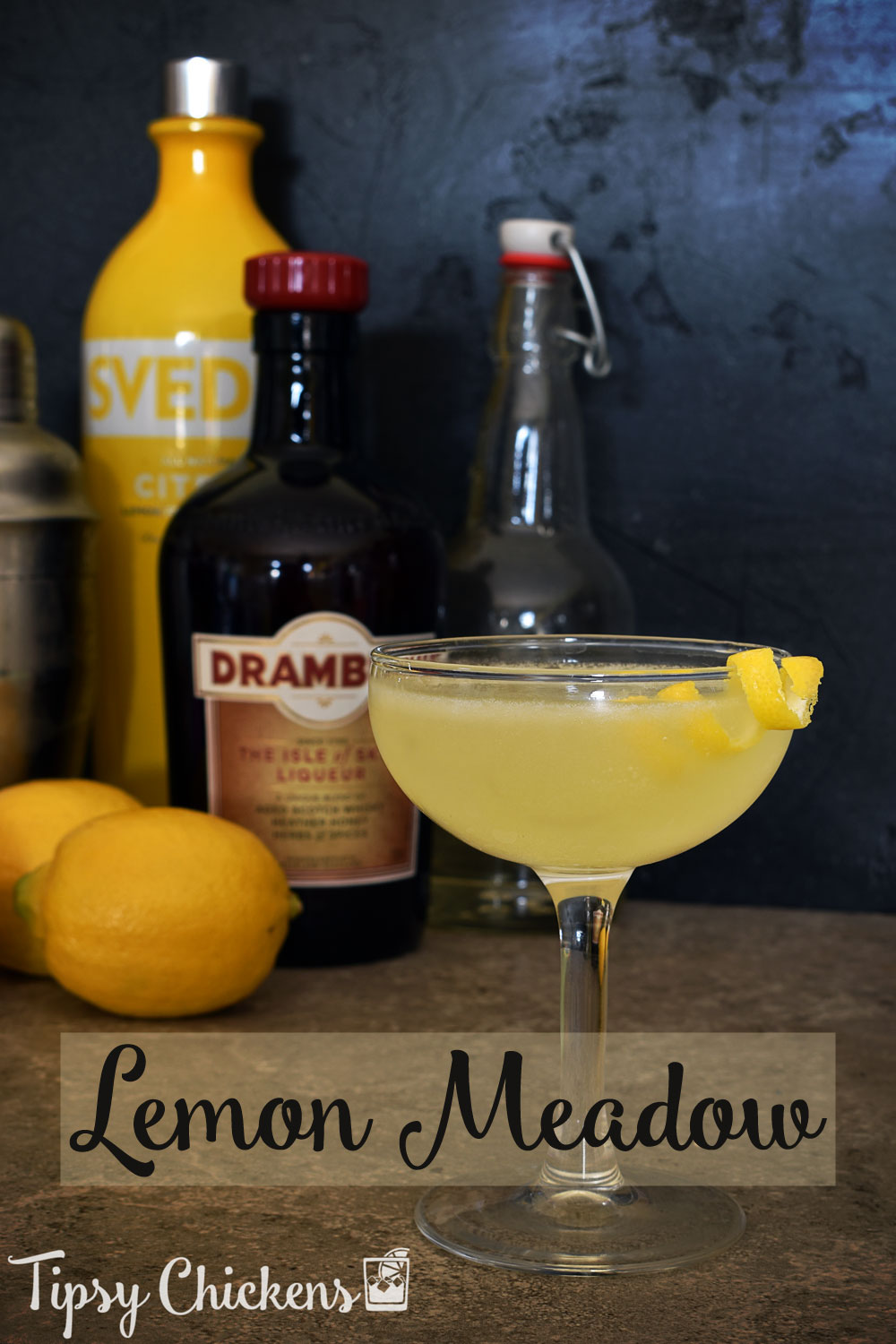 coupe glass with lemon meadow cocktail with lemon spiral garnish in foreground with citron lemon vodka, Drambuie, lemons, simple syrup in a flip top bottle and a silver cocktail shaker in the background